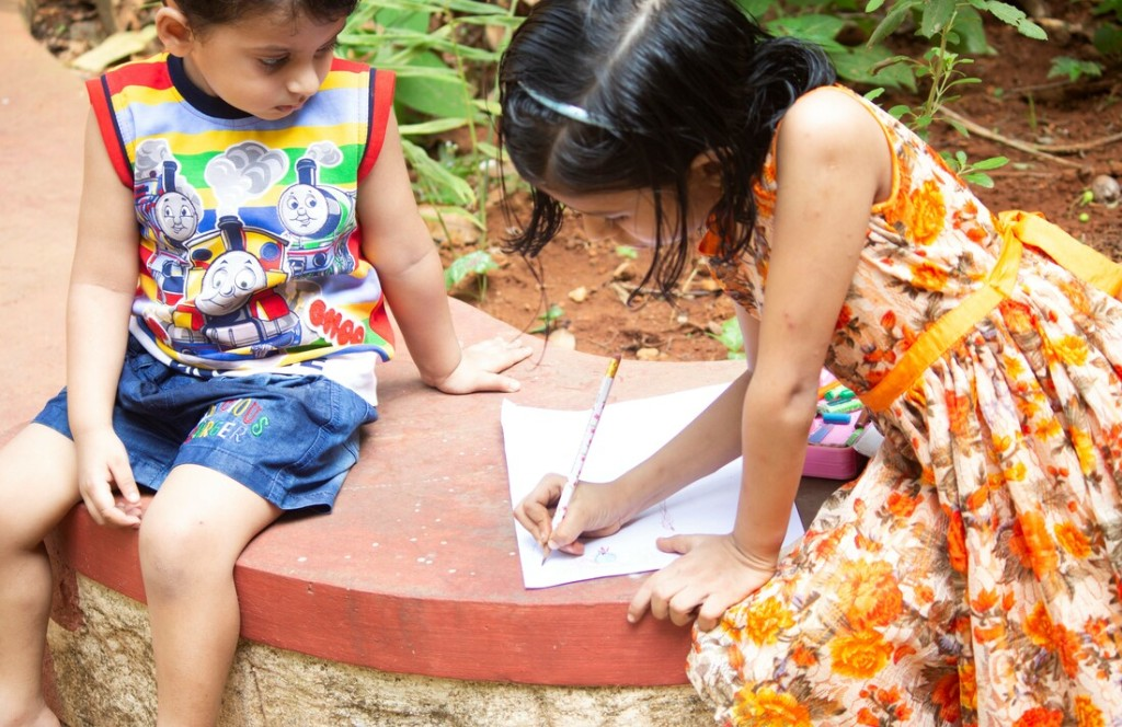Two children writing on paper